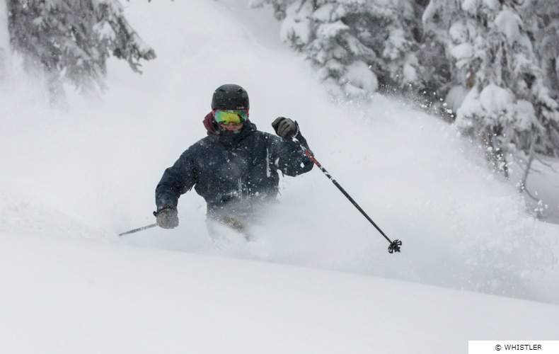 A skier in black with mirrored visor and ski poles navigates some fresh powder snow