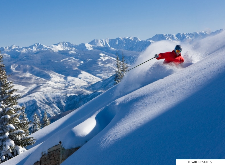 Skier in red carves on the mountain side under blue skies with the Beaver Creek ski area in the background