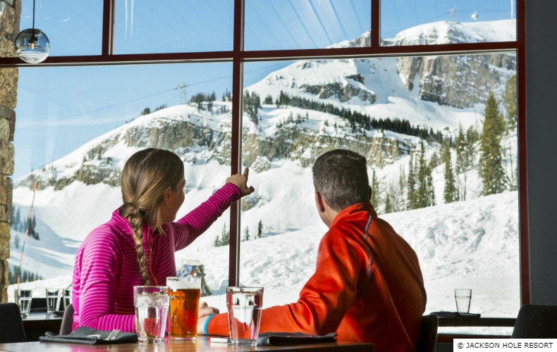 A couple enjoying drinks look out and up a snow covered mountain
