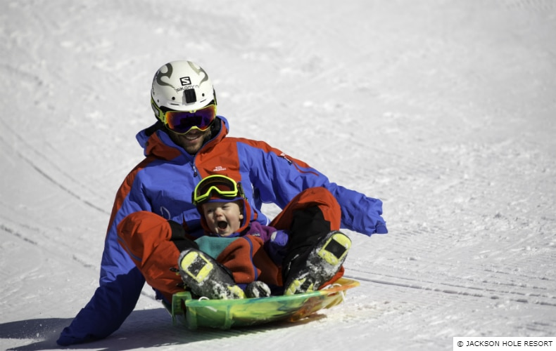A father and young child laughing as they slide down a slope on a plastic sled