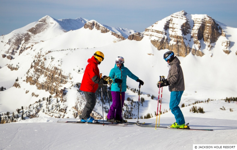 3 skiers having a conversation before descending the mountain