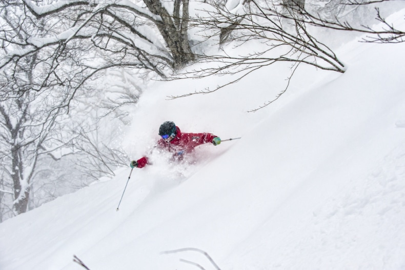 A skier in red descends a mountain at Myoko Kogen ski resort in Japan