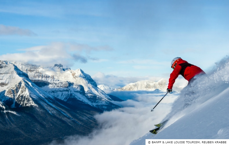 A skier in red at Lake Louise Ski Resort descends the mountain with blue skies and Canada's Rocky Mountains in the background