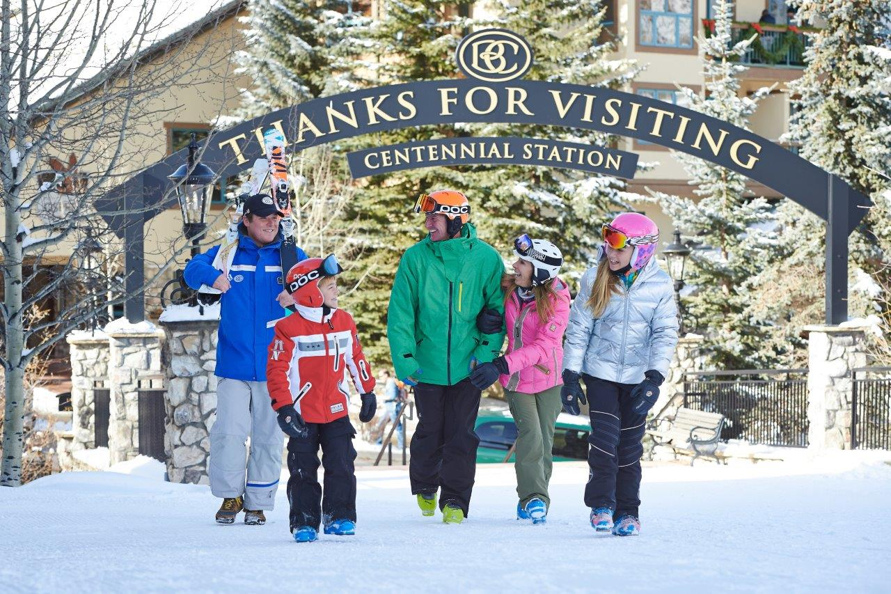 Family in brightly colored ski gear leaves Centennial Station at Beaver Creek Ski Resort