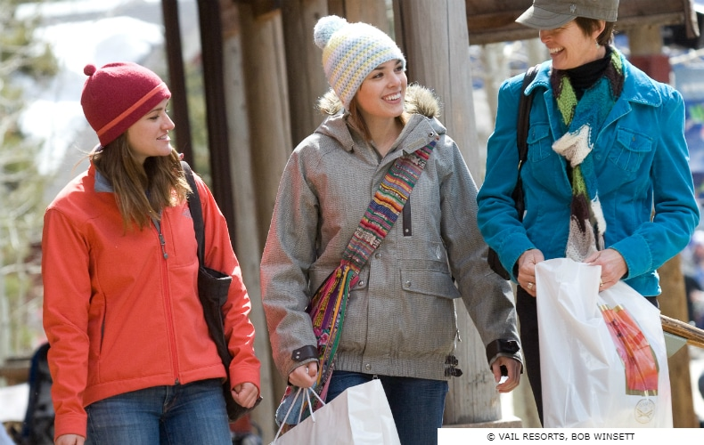 3 smiling friends in jackets and beanies carry shopping bags