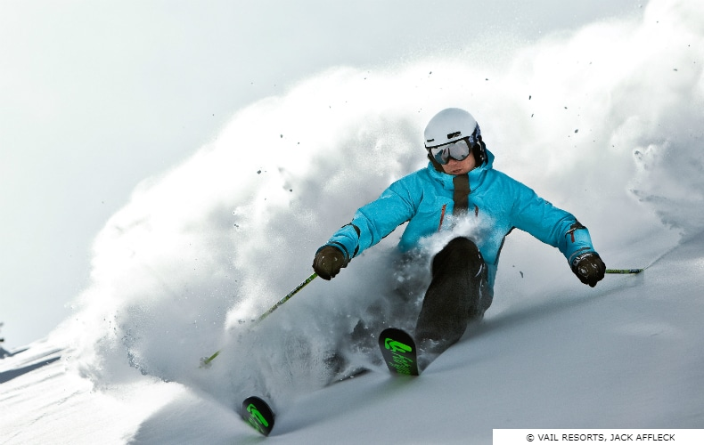 Skier in blue jacket and googles throws powder during a turn