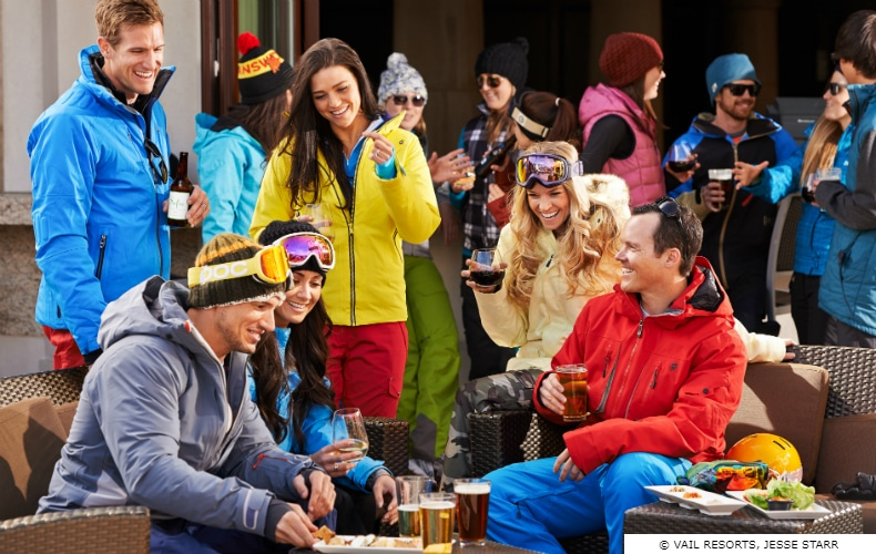 3 young couple in brightly colored ski gear enjoying some Apres Ski food & drinks