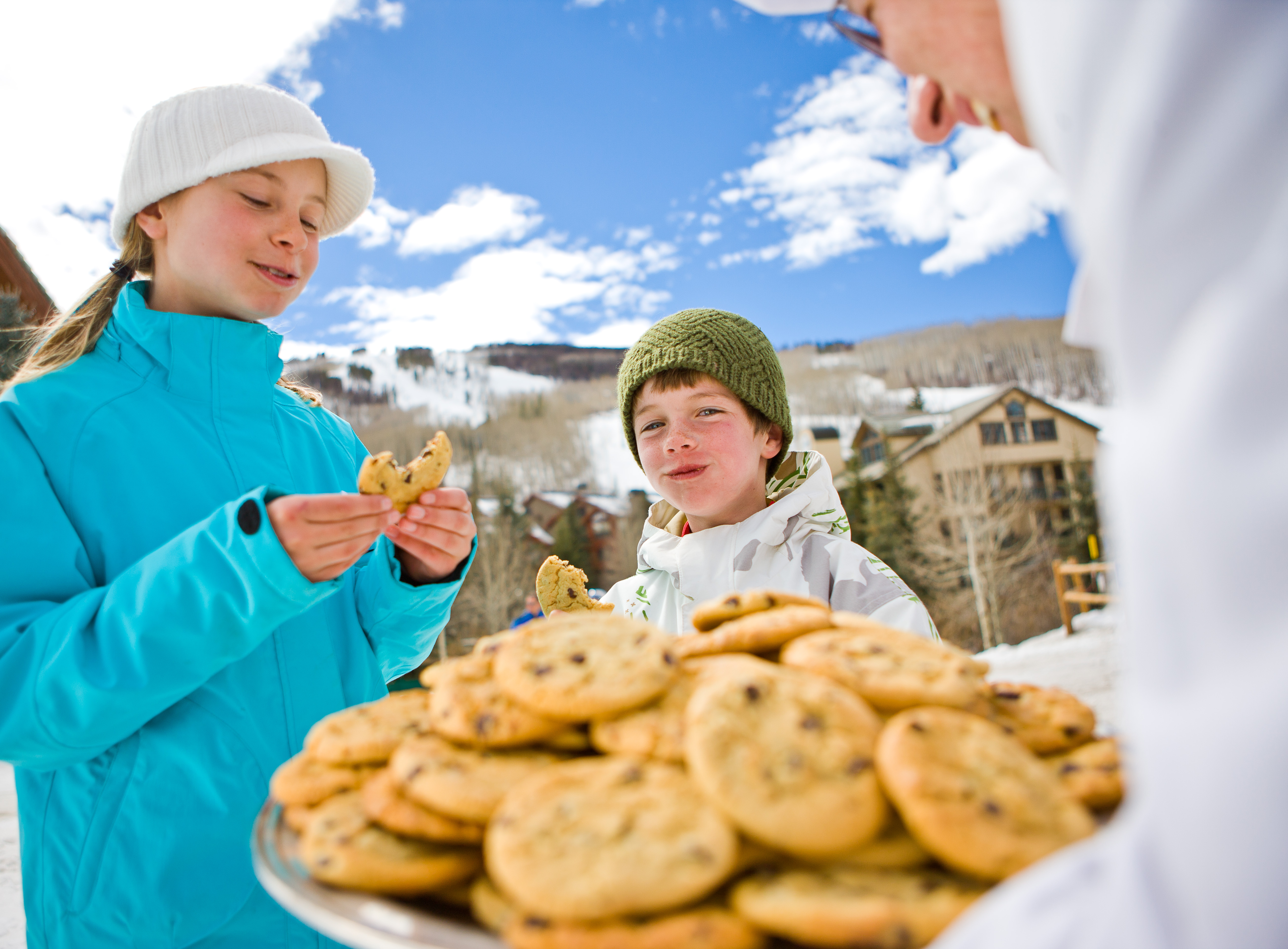Young girl and boy with cheeky grins enjoying a plate of choc chip cookies